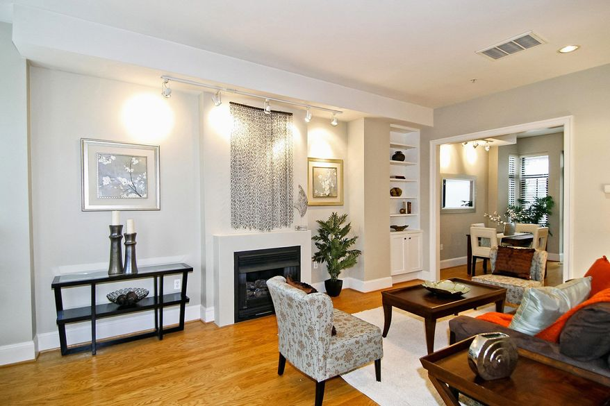 The living room has a gas fireplace, track lighting and built-in bookshelves. The home's first and second levels have hardwood floors.