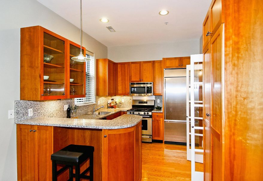 The kitchen has cherry cabinets, stainless steel appliances, granite counters and a granite breakfast bar.