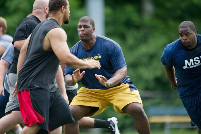 ROD LAMKEY JR./THE WASHINGTON TIMES Redskins lineman Selvish Capers (right) practices an offensive line drill during an informal workout at a Northern Virginia facility. Washington's offensive line ranked 23rd in the NFL last season in sacks per pass play.