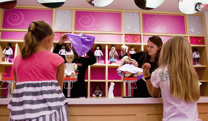 Sisters Tess (left), 8, and Sophie McMullen, 7, from Leesburg, Va., watch stylists work on their dolls in the Doll hair salon at American Girl during the store's soft opening at Tysons Corner Center in McLean on Thursday. The grand opening is Saturday. (Pratik Shah/The Washington Times)