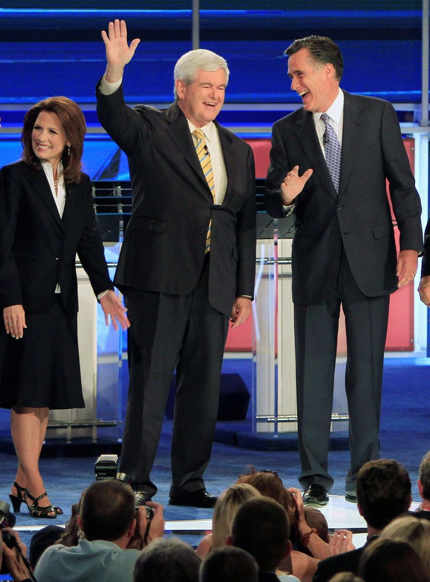 Former Massachusetts Gov. Mitt Romney (right) and former House Speaker Newt Gingrich share a laugh and acknowledge the audience before the first New Hampshire Republican presidential debate at St. Anselm College in Manchester on Monday. Rep. Michele Bachmann of Minnesota (left), officially declared her candidacy during the evening. (Associated Press)