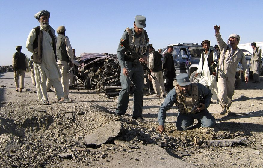 Afghan police officers inspect the site of a blast in the central province of Ghazni, Afghanistan, Saturday, June 18, 2011. Two roadside bomb attacks on Saturday killed four private security guards escorting supply convoys for a NATO base in eastern Afghanistan, a police chief said. (AP Photo/Rahmatullah Nikzad)