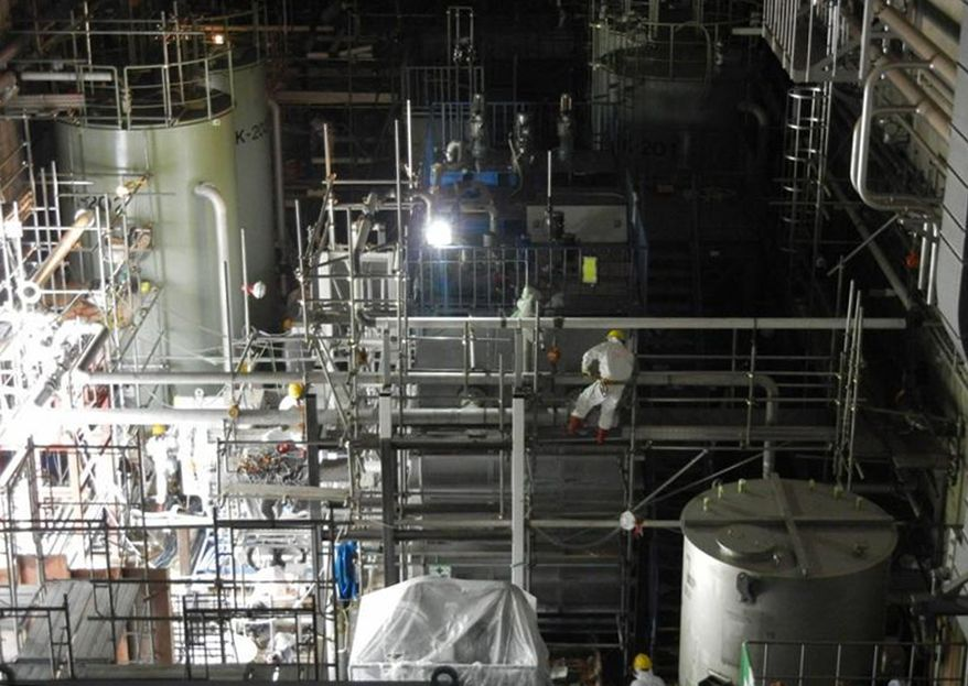 ** FILE ** In this May 31, 2011, photo released Saturday, June 4, 2011, by Tokyo Electric Power Co. (TEPCO), a worker climbs scaffoldings set up around the decontamination device, having functions of nuclide adsorption and coagulation settling in the newly built radioactive water processing facilities at Fukushima Dai-ichi nuclear power plant in Okuma, Fukushima prefecture, northeastern Japan. (AP Photo/Tokyo Electric Power Co.)