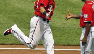 Washington Nationals' Michael Morse, left, is congratulated by third base coach Bo Porter, right, as he rounds the bases after hitting a two-run home run off Baltimore Orioles pitcher Brian Matusz during the sixth inning of an interleague baseball game in Washington, Saturday, June 18, 2011. The Nationals beat the Orioles 4-2. (AP Photo/Ann Heisenfelt)