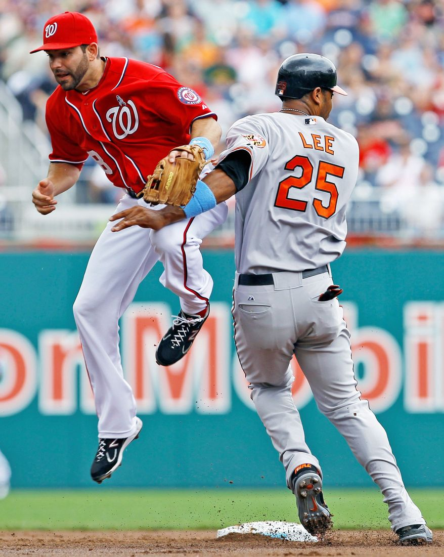 Baltimore Orioles' Derrek Lee (25) is safe at second base as he collides with Washington Nationals second baseman Danny Espinosa while advancing on a throwing error by third baseman Ryan Zimmerman during the second inning of a baseball game in Washington, Sunday, June 19, 2011. (AP Photo/Ann Heisenfelt)