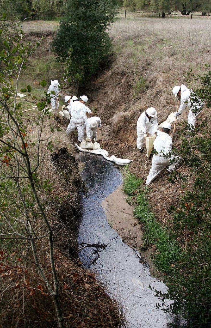 A Greka Oil & Gas cleanup crew works on an oil spill flowing down a creek behind Firestone Vineyard, north of Los Olivos, Calif. in January 2008. The the company is blamed for 21 spills of crude oil and other pollutants in Santa Barbara County waterways, leading to a lawsuit filed Friday by the U.S. Department of Justice and state and federal environmental regulatory agencies. (Santa Barbara County Fire Department via Associated Press)