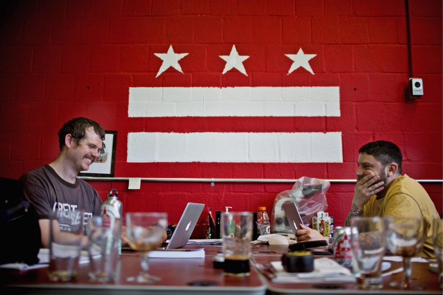 DC Brau President Jeff Hancock (left) and CEO Brandon Skall work at their computers in the office of their Bladensburg Road NE brewery and warehouse in the District recently. (Drew Angerer/The Washington Times)