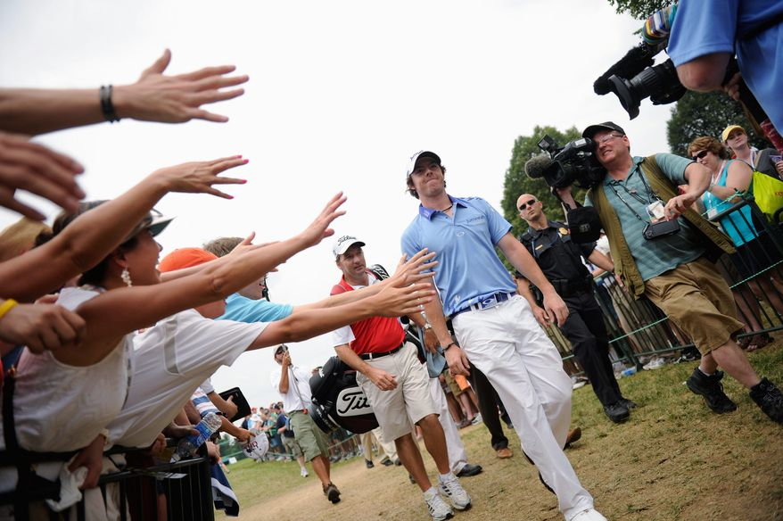 "PHOTOGRAPHS BY DREW ANGERER/THE WASHINGTON TIMES Fans hold out their hands to try to to touch tournament leader Rory McIlroy of Northern Ireland as he makes his way from the practice range to the first tee before starting his final round at the U.S. Open. McIlroy went on to win by finishing with a tournament-record score of 268. ""What he is doing is pretty special,"" said world No. 1 Luke Donald."