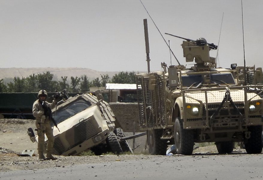 A German soldier with the NATO-led International Security Assistance Force (ISAF) guards a road at the site of a suicide attack on a German military convoy, in Kunduz, north of Kabul, Afghanistan on June 19, 2011. (Associated Press)