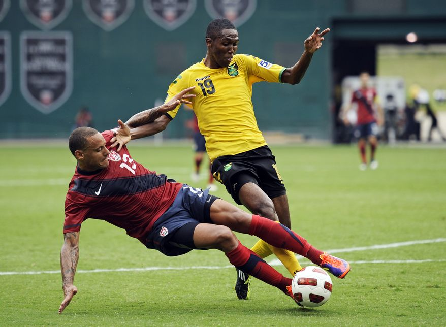 Jamaica's Dwayne Miller (19) battles United States' Jermaine Jones for the ball near Jamaica's goal during the first half of a CONCACAF Gold Cup quarterfinal Sunday at RFK Stadium. The U.S. won 2-0.  (AP Photo/Cliff Owen)