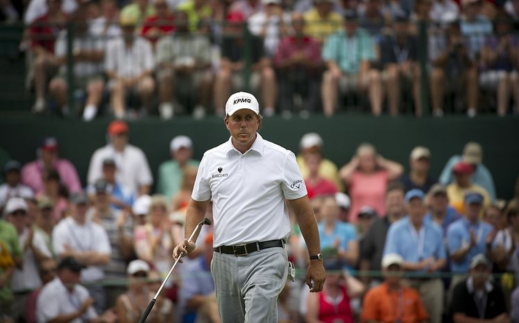 Phil Mickelson reacts after his putt on the sixth green as he makes his way to the seventh tee during the championship round of the 2011 U.S. Open Congressional, in Bethesda, Md., Sunday, Ju
