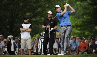 Amateur Patrick Cantlay, USA, hits off the first tee as his caddie Dane Jako, his high-school coach, and Peter Hanson, of Sweden, watch during the final round of the U.S. Open at Congressional Country Club in Bethesda, Md., Sunday, June 19, 2011. (Drew Angerer/The Washington Times)