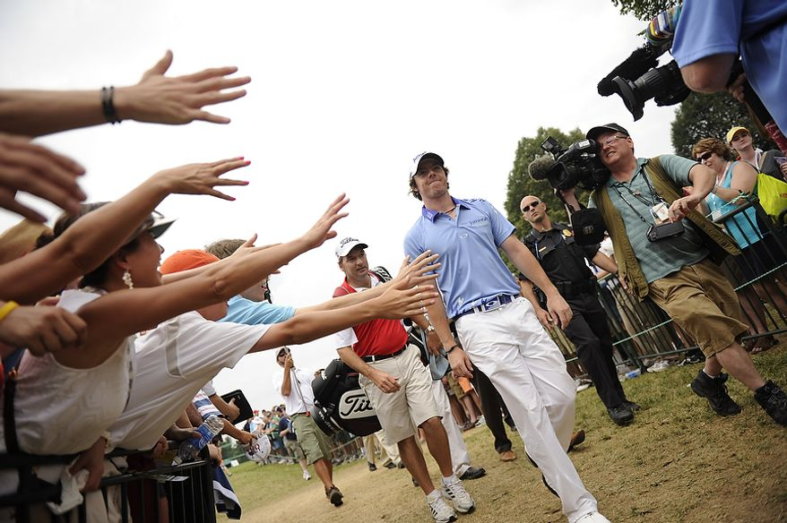 Fans hold out their hands to touch tournament leader Rory McIlroy, of Northern Ireland, as he makes his way from the practice range to the first tee before starting his final round of the U.S. Open at Congressional Country Club in Bethesda, Md., Sunday, June 19, 2011. (Drew Angerer/The Washington Times)