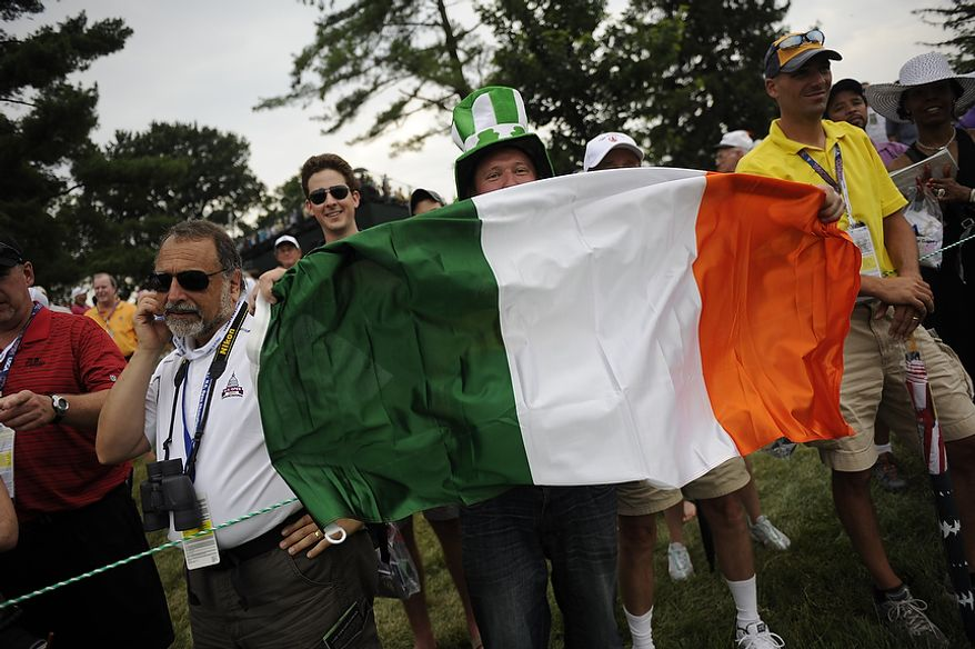 A fan waves and Irish flag on the first fairway during the final round of the U.S. Open at Congressional Country Club in Bethesda, Md., Sunday, June 19, 2011. (Drew Angerer/The Washington Times)