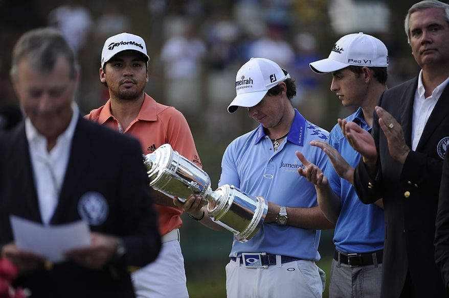 Rory McIlroy looks at the U.S. Open trophy after winning the championship at Congressional Country Club in Bethesda, Md., Sunday, June 19, 2011. (Drew Angerer/The Washington Times)