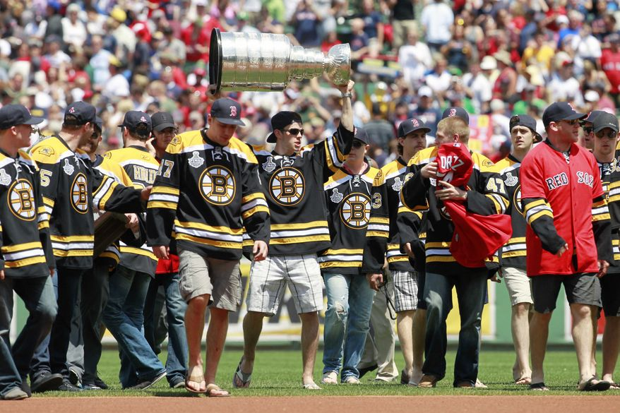 The Boston Bruins walk on to the field at Fenway Park with the Stanley Cup before an interleague baseball game between the Boston Red Sox and the Milwaukee Brewers in Boston, Sunday, June 19, 2011. (AP Photo/Michael Dwyer)