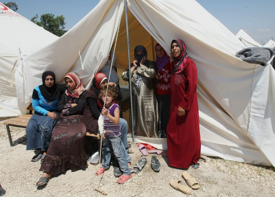 Refugee women look out from their tented home inside a Syrian refugee camp just at the border in Turkey near Turkish village of Boynuyogun in Hatay province, Turkey, on June 18, 2011, during a press tour organized by the Turkish authorities. (Associated Press)