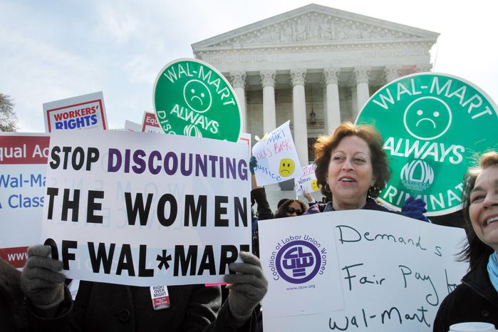 Carol Rosenblatt (right), of the District, takes part in a rally at the Supreme Court on March 29 in support of plaintiffs in a case of female employees against Wal-Mart.  The National Women's Law Center decried Monday's ruling, which held the