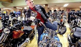 "ASSOCIATED PRESS Former Utah Gov. Jon Huntsman Jr., a Republican presidential hopeful and a former ambassador to China, swings his leg over a ""Deluxe Softail"" Harley during a stop at Manchester Harley-Davidson in New Hampshire this month."