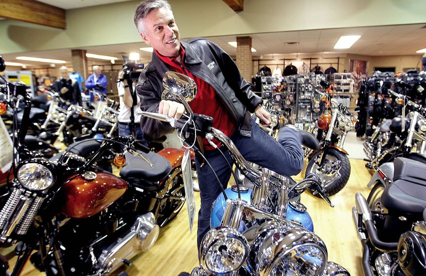 """ASSOCIATED PRESS Former Utah Gov. Jon Huntsman Jr., a Republican presidential hopeful and a former ambassador to China, swings his leg over a """"Deluxe Softail"""" Harley during a stop at Manchester Harley-Davidson in New Hampshire this month."""