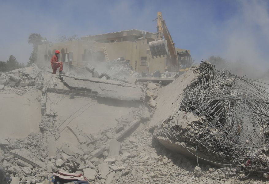 Firefighters work in the rubble of a destroyed building in the Galil compound in Surman, Libya, some 40 miles west of Tripoli, on Monday, June 20, 2011, in this photo taken on a government-organized tour. (AP Photo/Ivan Sekretarev)