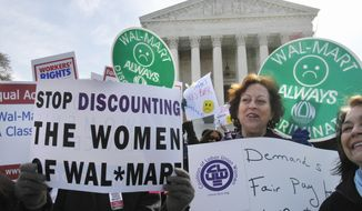 **FILE** In this photo from March 29, 2011, Carol Rosenblatt (right), of Washington, and others take part in rally outside the Supreme Court in support of the plaintiffs in a case of women employees against Wal-Mart. (Associated Press)