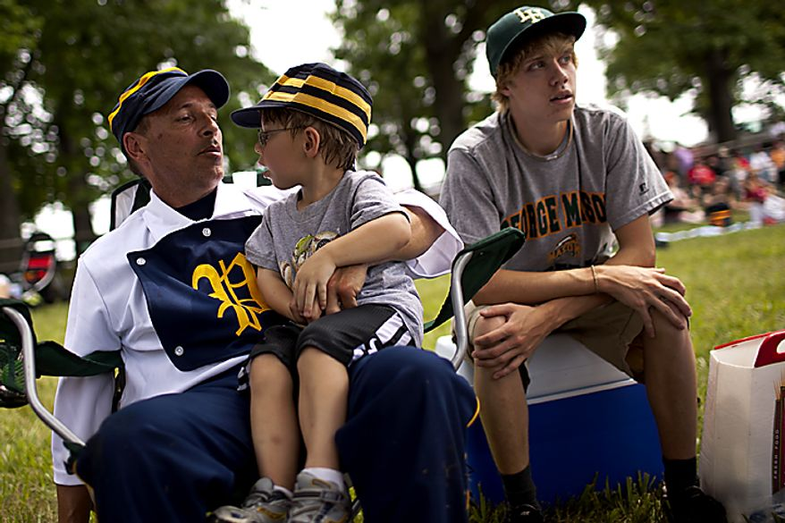 """Potomac Nine pitcher J.D. """"Buckeye"""" Almond, of Marshall, Va., sits with his son Wyatt on his lap as they watch the games during the Loudoun Preservation Society's 19th Century Baseball Day at the Oatlands, in Leesburg, Va., Sunday, June 12, 2011. (Drew Angerer/The Washington Times)"""