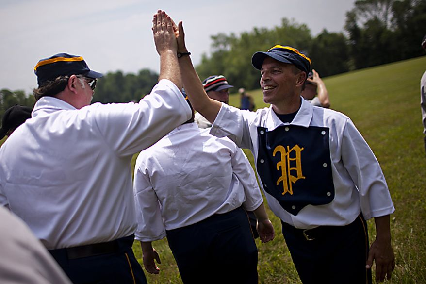 "Potomac Nine pitcher J.D. ""Buckeye"" Almond, of Marshall, Va., gives a high five to Gene ""Pop"" Meacham, of Bowie, after their 5-4 win over the Elkton Eclipse during the Loudoun Preservation Society's 19th Century Baseball Day at the Oatlands, in Leesburg, Va., Sunday, June 12, 2011. Almond said this is his fourth year playing in the league. He said he took up vintage baseball after playing in independent minor leagues and blowing out his knee. (Drew Angerer/The Washington Times)"