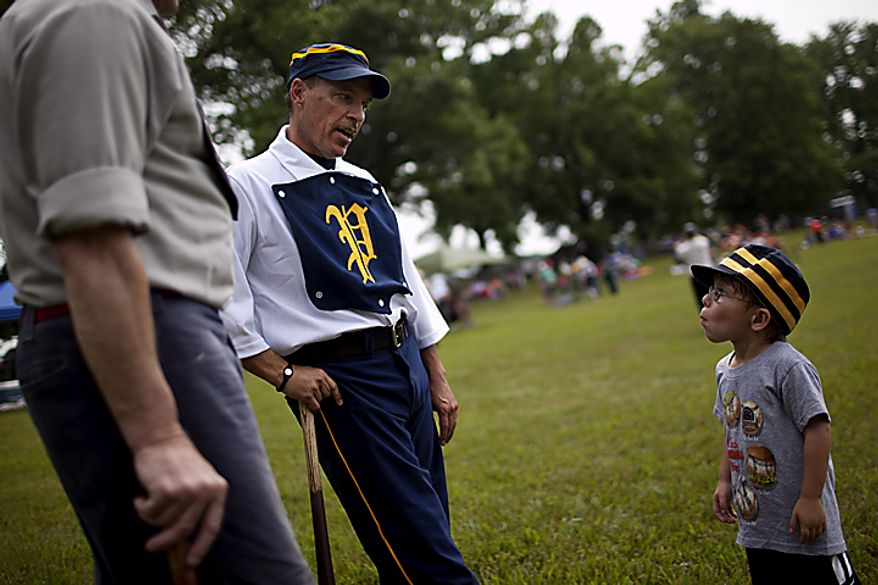 """Potomac Nine pitcher J.D. """"Buckeye"""" Almond, of Marshall, Va., talks to his son Wyatt, at right, before the games started at the Loudoun Preservation Society's 19th Century Baseball Day at the Oatlands, in Leesburg, Va., Sunday, June 12, 2011. Almond had many friends and family on hand to watch, as historically the day was a social affair. (Drew Angerer/The Washington Times)"""