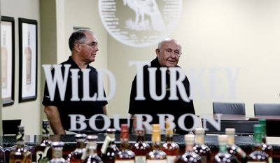 Master distiller Jimmy Russell (right) and his son Eddie are reflected in a mirror in the Wild Turkey Distillery offices in Lawrenceburg, Ky. Times are good for bourbon distilleries because of an increasing worldwide thirst for Kentucky's signature liquor. (Associated Press)