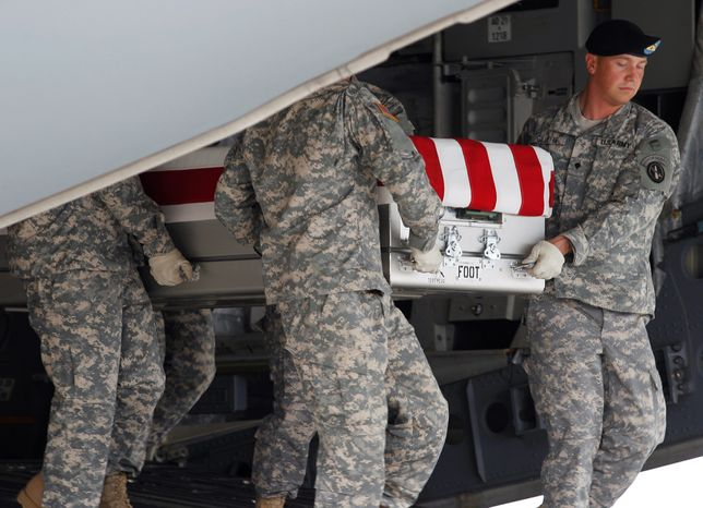 An Army carry team carries the transfer case containing the remains of Army Pfc. Brian J. Backus of Saginaw Township, Mich., upon arrival at Dover Air Force Base, Del. on Tuesday, June 21, 2011. The Department of Defense announced the death of Backus who was supporting Operation Enduring Freedom in Afghanistan.(AP Photo/Jose Luis Magana)