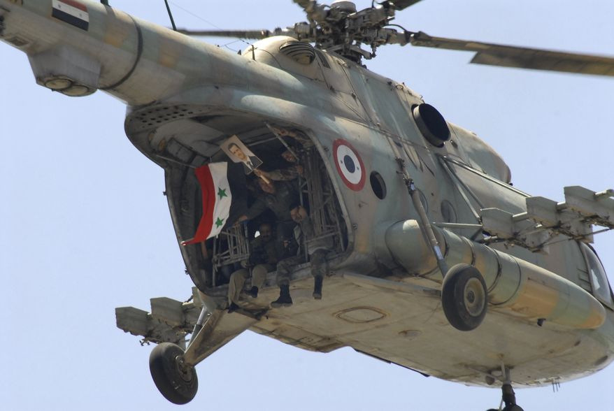 Syrian soldiers on board a helicopter carry a national flag and a picture of Syrian President Bashar Assad during a rally in support of Assad in Damascus, Syria, on June 21, 2011. (Associated Press)