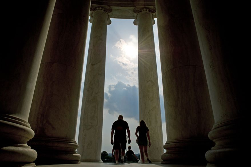 Tourists are silhouetted against a late afternoon sky in between the columns at the Jefferson Memorial on the longest day of the year, the Summer Solstice, in Washington, D.C., Tuesday, June 21, 2011. (Rod Lamkey Jr./The Washington Times)
