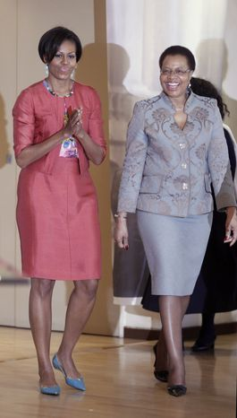 U.S. first lady Michelle Obama walks with Graca Machel, the wife of former South African President Nelson Mandela, as she visits the Nelson Mandela Foundation in Johannesburg on Tuesday, June 21, 2011. (AP Photo/Charles Dharapak, Pool)