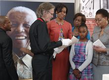 Verne Harris (second from left) shows artifacts from former South African President Nelson Mandela's imprisonment to (from third from left) U.S. first lady Michelle Obama; her mother, Marian Robinson; her daughter Sasha; and Graca Machel, Mr. Mandela's wife, during a visit to the Nelson Mandela Foundation in Johannesburg on Tuesday, June 21, 2011. (AP Photo/Charles Dharapak, Pool)