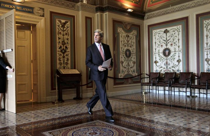 """Senate Foreign Relations Committee Chairman John Kerry, Massachusetts Democrat, walks to the floor of the Senate on Capitol Hill on June 21, 2011, where he introduced a bipartisan resolution to authorize continued use of """"limited"""" U.S. military force in Libya. (Associated Press)"""