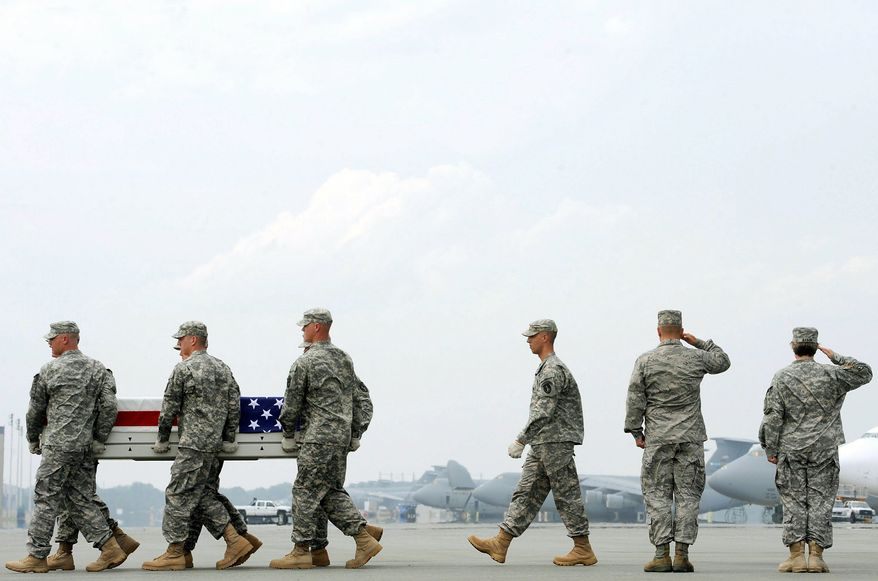 "ASSOCIATED PRESS SACRIFICE: Army soldiers carry a casket containing the remains of Sgt. James W. Harvey II on Wednesday at Dover Air Force Base in Delaware. The remainder of the 33,000 troop ""surge"" that President Obama ordered to Afghanistan in December 2009 will be withdrawn before September 2012."