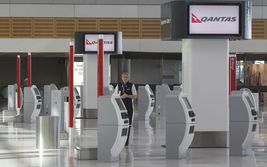 A sole Qantas worker stands at an empty check-in terminal at Sydney Airport, Australia, Tuesday, June 21, 2011. Several international and domestic flights through Australian airports were canceled Tuesday due to an ash cloud from a Chilean volcano moving into the country's airspace. (AP Photo/Rob Griffith)