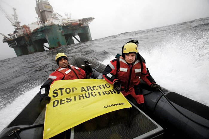 Greenpeace International global chief Kumi Naidoo (left) and an unidentified acquaintance make their view known on a boat near an oil rig in the Davis Strait, off Greenland's west coast, on Friday. Greenpeace said Mr. Naidoo was making a third attempt to stop a Scottish oil company from dee