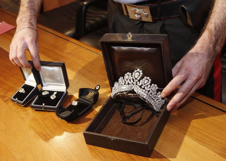 An Italian Carabinieri police officer shows recovered jewelry said to have belonged to the late Argentine first lady Eva Peron that was stolen from a store in Spain nearly two years ago, during a press conference in Milan, Italy, on June 22, 2011. (Associated Press)
