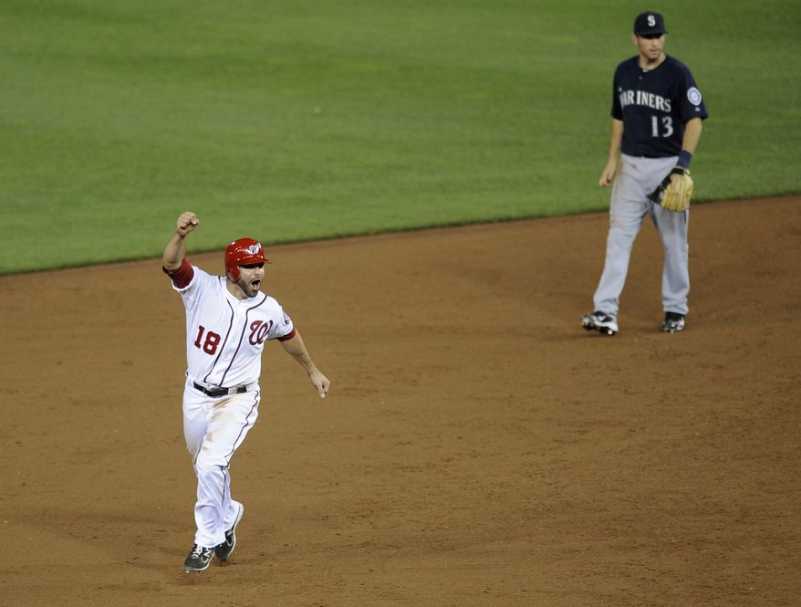 Washington Nationals' Danny Espinosa (18) celebrates as he rounds the bases on Wilson Ramos' three-run home run as Seattle Mariners second baseman Dustin Ackley (13) looks on during the ninth inning of a baseball game Tuesday, June 21, 2011, in Washington. The Nationals won 6-5. (AP Photo/Nick Wass)