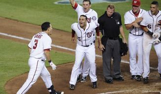 Washington Nationals' Wilson Ramos (3) is greeted by teammates after he hit a three-run home run during the ninth inning to give the Nationals a 6-5 win over the Seattle Mariners in a baseball game Tuesday, June 21, 2011, in Washington. (AP Photo/Nick Wass)
