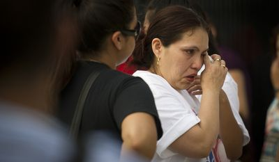 Judith Fernandez, sister of crash victim Ana Fernandez, wipes tears from her eyes as she spends time at a personal memorial to her sister and several of the other victims, on The Charles A. Langley Bridge near the Fort Totten Metro Station. (Rod Lamkey Jr./The Washington Times)