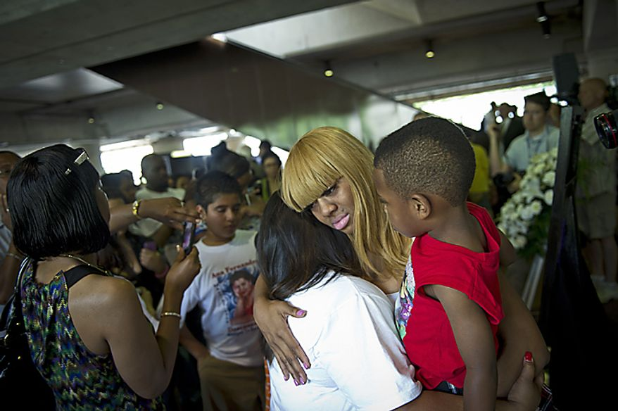 "Keonda King, whose younger sister, Lavonda ""Nikki"" King, was among nine people killed in a June 22, 2009, Metrorail crash, holds her sister's son Emmanuel, 7, as she hugs Evelyn Fernandez (in white), whose mother was killed in the crash, during a memorial service and wreath laying ceremony at the Fort Totten Metrorail Station in Washington, D.C., on June 22, 2011. (Rod Lamkey Jr./The Washington Times)"