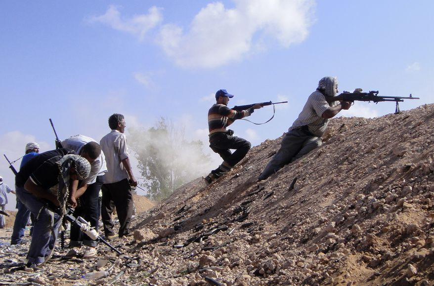** FILE ** Libyan rebel fighters fire toward forces loyal to Col. Moammar Gadhafi on the front line of Dafniya in Misrata, Libya, on Tuesday, June 21, 2011. (AP Photo/Abdel-Kader Fassouk)