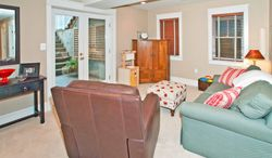 The lower-level recreation room has glass doors that open to steps leading to the flagstone patio and backyard.