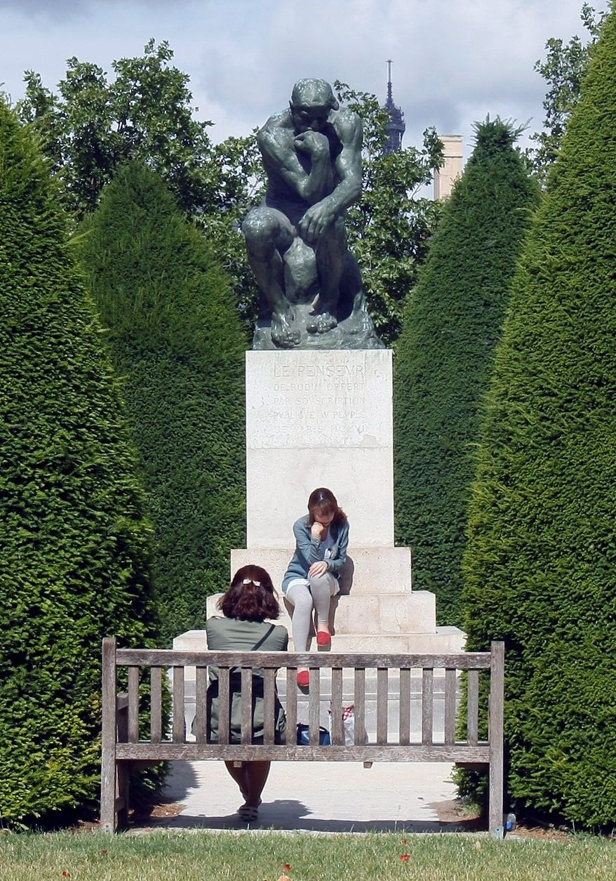 """ASSOCIATED PRESS PHOTOGRAPHS A visitor mimics the iconic pose of Auguste Rodin's """"The Thinker"""" in the garden of the Musee Rodin, the kind of out-of-the-way place Woody Allen celebrates in """"Midnight in Paris."""" The boutique of the Deyrolle taxidermist is another, offering animals of all sizes. Dating from 1831, the place is imbued with history and magic."""
