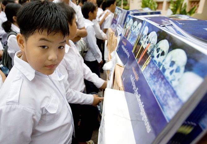 Associated Press photographs Cambodian students look at books about the Khmer Rouge at a high School in Phnom Penh. Eight years after the creation of a U.N.-backed multinational panel to hold trials on the regime, it is riven by suspicion.
