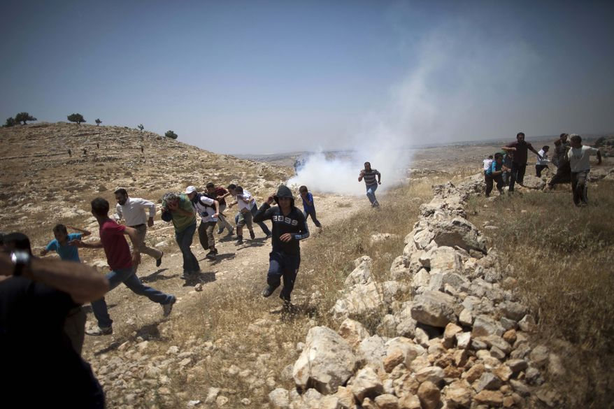 **FILE** Palestinians run from tear gas fired by Israeli soldiers during a demonstration against the expansion of nearby settlements at the West Bank village of Dier Qadis, near Ramallah, on June 15, 2011. (Associated Press)