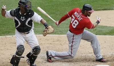Washington Nationals' Michael Morse, right, knees down after striking out as Chicago white Sox catcher Ramon Castro looks to throw a ball during the seventh inning of an interleague baseball game in Chicago, Saturday, June 25, 2011. The White Sox won 3-0. (AP Photo/Nam Y. Huh)